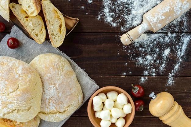 Свежеиспеченный итальянский белый хлеб - чиабатта, шарики моцареллы на дереве. вид сверху.
