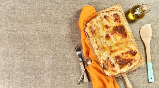 Свежеиспеченная лазанья с плавленым сыром на деревенском столе
