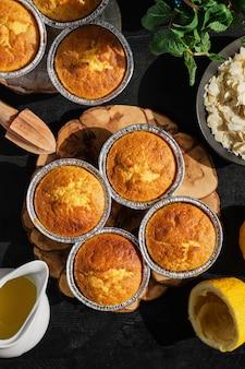 Muffin al limone appena sfornati sulla tavola di legno nera