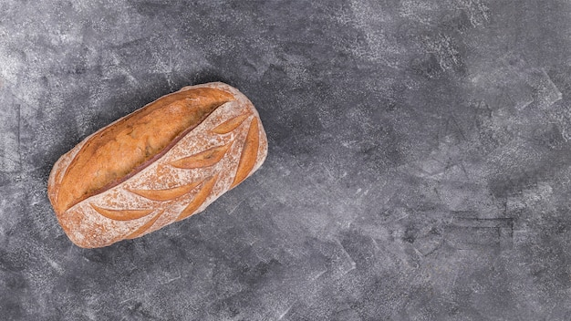 Freshly baked loaf of bread on black textured background