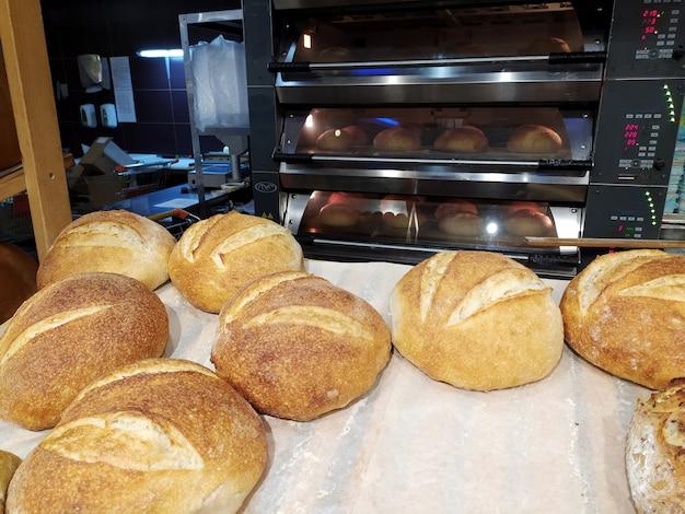 焼きたてのパンはパン屋のトレイにあり、背景には熱いオーブンがあります。