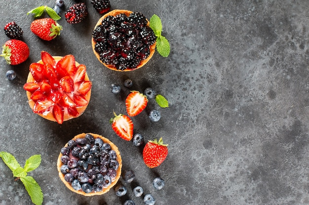테이블에 딸기와 갓 구운 미니 타르트. 여름 과일 굽기. 공간을 복사합니다. 평면도.