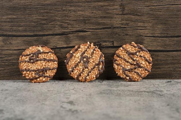 Biscotti di farina d'avena appena sfornati cosparsi di semi su marmo.