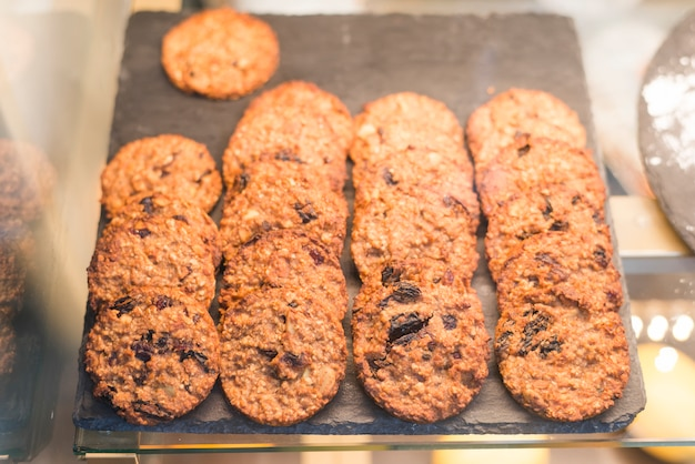 Freshly baked oatmeal raisin cookies on tray in the glass cabinet