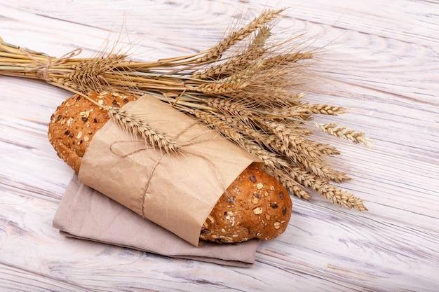 焼きたての有機サワードウパンをパン屋の持続可能な紙袋に入れます。分離された紙袋に入った焼きたてのそばパン1斤。白い表面に焼きたてのパンの塊。エコロジカルフード