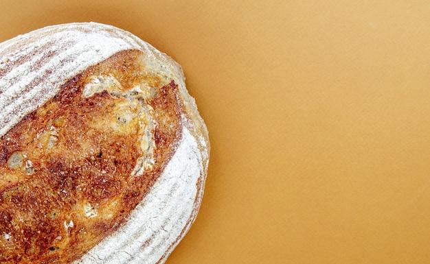 Свежеиспеченный органический хлеб на закваске, изолированные на коричневом или кофейном фоне. одна буханка вкусного свежего гречневого хлеба. экологическая еда. вид сверху, плоская планировка.