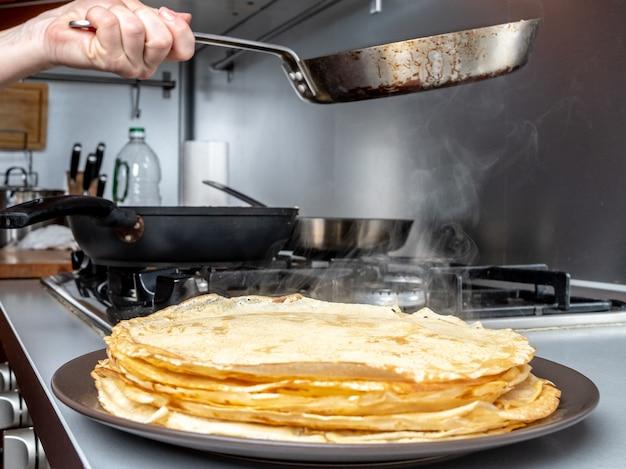 焼きたてのパンケーキを皿の上に積み上げ、ストーブの上に鍋を持っている人間の手の背景に蒸気が当たる。パンケーキウィークの休日のための伝統的な御馳走。