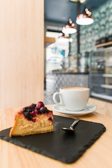 Freshly baked pastry with cup of coffee on wooden table