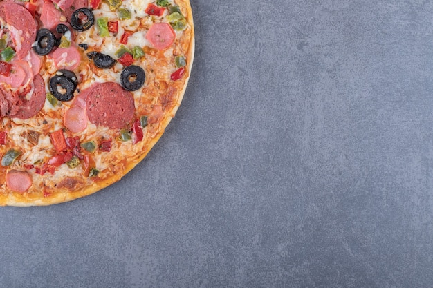 Freshly baked pepperoni pizza on grey background.