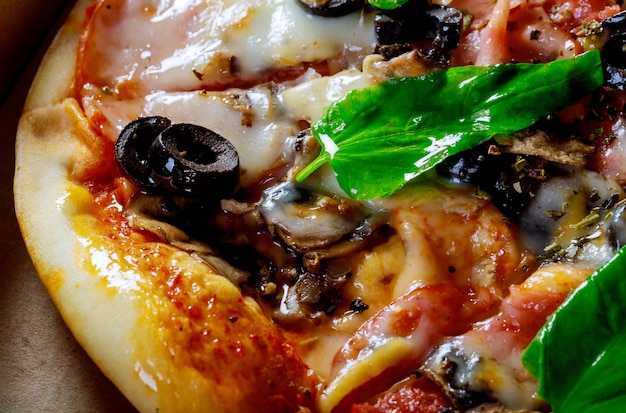 Freshly baked pizza and its components with black olives basil leaves boiled corn