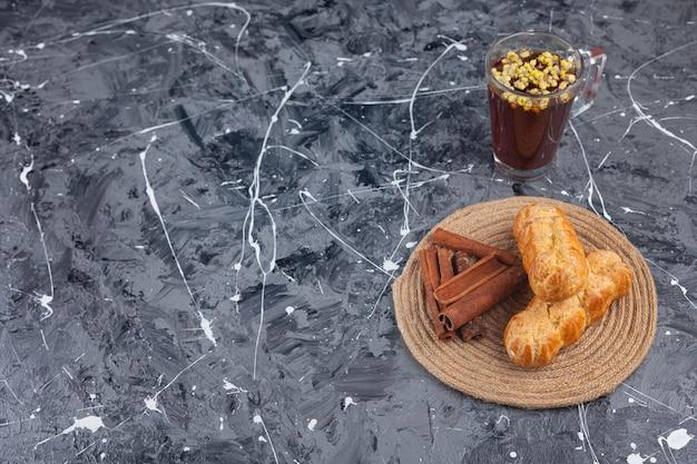 Freshly baked plain eclairs with cinnamon sticks.