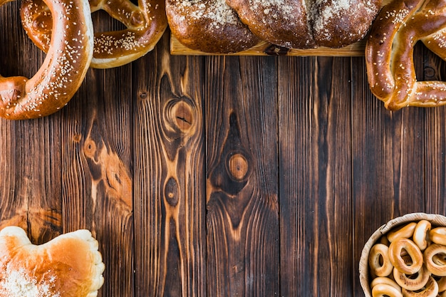 Freshly baked plaited loaf and pretzels on the wooden table with copy space