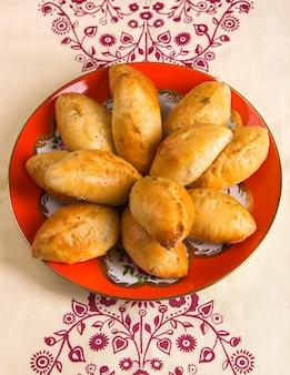 Свежеиспеченные румяные пироги лежат в тарелке, стоящей на скатерти с узором