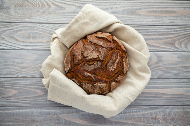 木製の背景にリネン布で焼きたてのライ麦パン