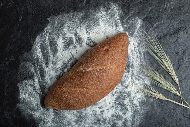검은 배경에 갓 구운 호밀 빵