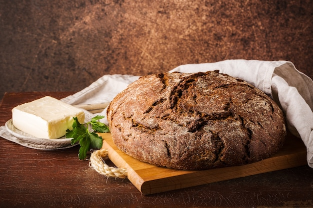나무 판자에 갓 구운 호밀 빵, 면 냅킨, 버터 접시에 버터, 파슬리 조각, 텍스트를 위한 공간. 갈색 배경을 닫습니다.
