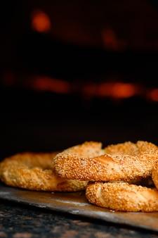 Свежеиспеченная выпечка симит с семенами кунжута крупным планом (турецкий бублик - геврек или кулури) перед очагом. традиционный белый хлеб с кунжутом на завтрак, крупным планом