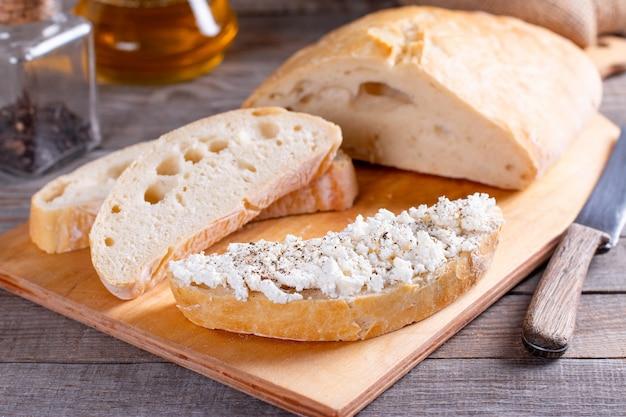 カッテージチーズ、チャバタと木のまな板の上で焼きたてのスライスされたパン
