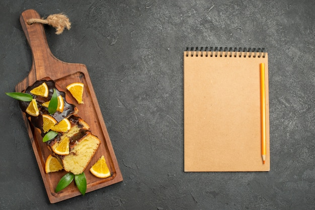 Freshly baked soft cake slices on wooden cutting board and notebook on dark table