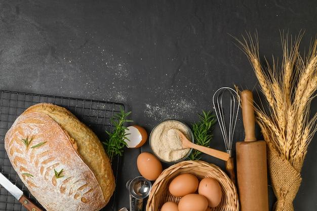 焼きたてのサワードウパン、新鮮な卵とアクセサリーベーカリー、黒いテーブル、上面図、コピースペース
