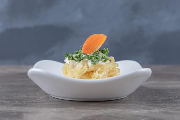 Spaghetti appena sfornati con la carota alla piastra, sul marmo. foto di alta qualità