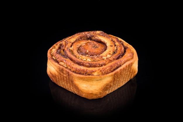 黒の背景に分離されたレーズンとシナモンと焼きたての甘いパン。自家製の伝統的なパン屋、パンとお菓子のコンセプトを焼く。