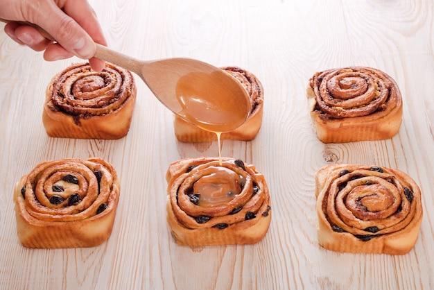 木製のテーブルにレーズンとシナモンを添えた焼きたての甘いパン。シナボンのグレージングが勝ちました。自家製の伝統的なパン屋、パンとお菓子のコンセプトを焼く。