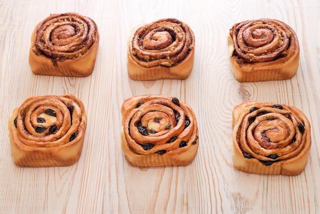 木製のテーブルにレーズンとシナモンを添えた焼きたての甘いパン。自家製の伝統的なパン屋、パンとお菓子のコンセプトを焼く。