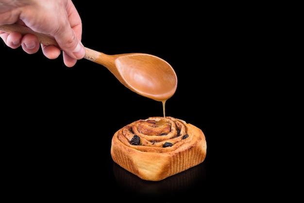 黒の背景に分離されたレーズン、シナモン、甘い釉薬と焼きたての甘いパン。自家製の伝統的なパン屋、パンとお菓子のコンセプトを焼く。