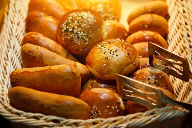 木製の籐のかごにチョコレートとココナッツのパン粉を入れた焼きたての甘いパイ生地のパンがすぐに食べられます。朝食またはブランチの概念。ウェブサイトまたはバナーの背景。コピースペース