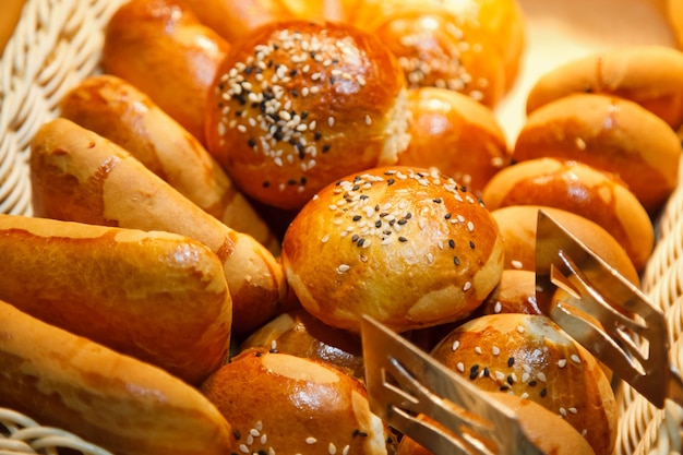 Свежеиспеченные сладкие булочки из слоеного теста с шоколадной и кокосовой крошкой в деревянной плетеной корзине готовы к употреблению. концепция завтрака или позднего завтрака