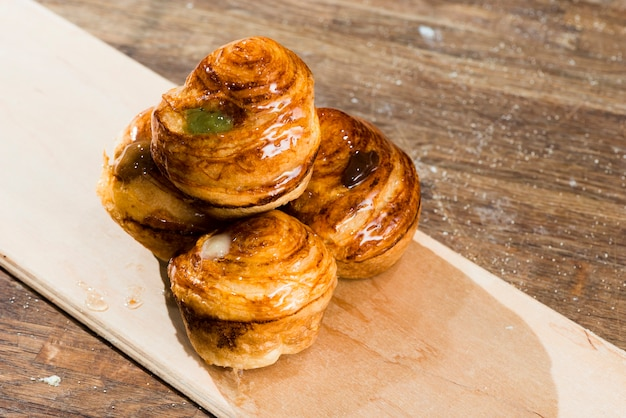 Freshly baked sweet puff pastry on plank over the wooden desk