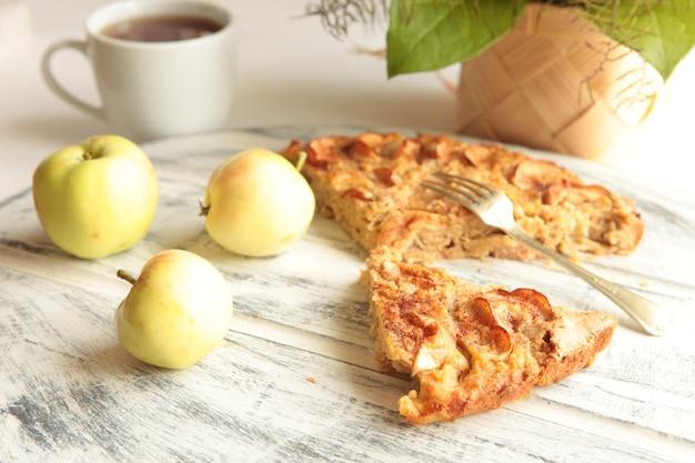 백그라운드에서 사과와 차 컵과 함께 갓 구운 맛있는 사과 파이. 집에서 만든 건강식
