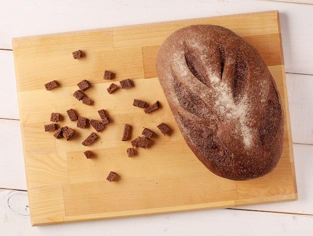 Свежеиспеченный традиционный хлеб и крекеры на разделочной доске