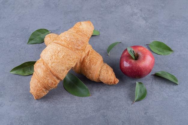 갓 구운 두 개의 크루아상과 유기농 빨간 사과
