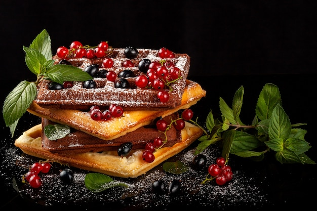 Freshly baked viennese waffles lie on a black table.