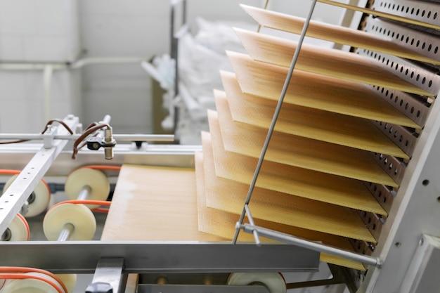 焼きたてのウエハースシートが製菓工場のコンベアに沿って上昇します