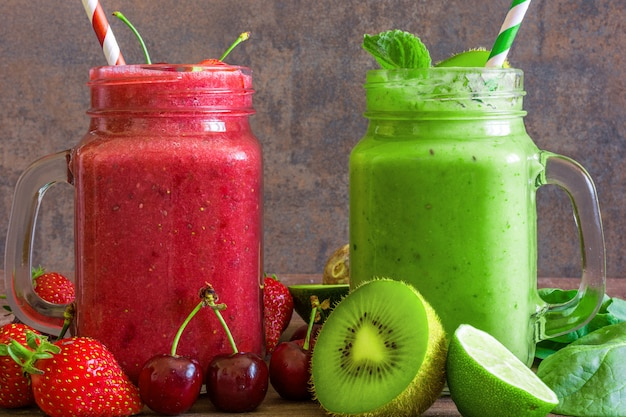Freshly blended fruit and vegetable smoothies in glass jars on rustic wooden background
