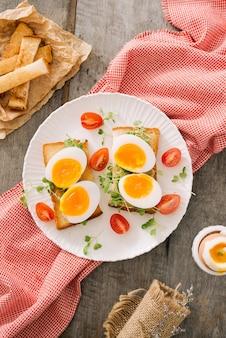 木の板にゆでたての白卵。健康的なフィットネスの朝食。