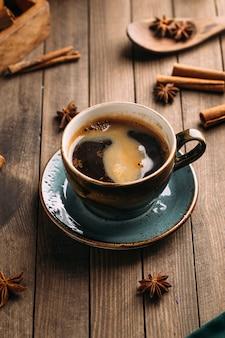 Свежезаваренный ароматный черный кофе на темном деревянном столе, украшенном специями