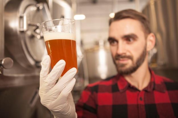 Свежезаваренное пиво в стеклянной пивоварне держит