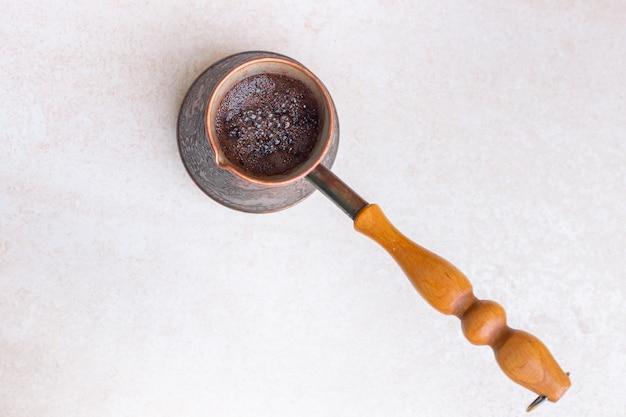 ライトテーブルトップビューの朝の爽快なドリンクに金属製のタークで淹れたてのブラックコーヒー