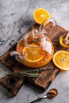 Freshly brewed buckthorn tea in a transparent teapot with fruits