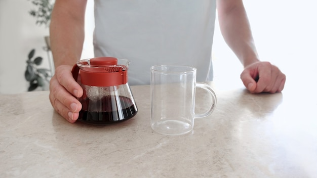 Freshly brewed coffee in glass server and glass cup on table. pourover, v60.