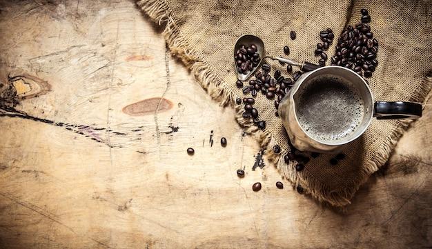 Свежезаваренный кофе в кувшинах на старом мешке.
