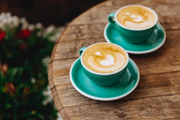 Свежезаваренный кофе с сердечком сверху в двух кружках бирюзового цвета на блюдцах на деревянном круглом столе