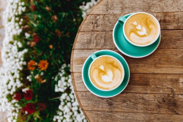 Свежезаваренный кофе в форме сердца в двух светло-зеленых чашках на блюдцах