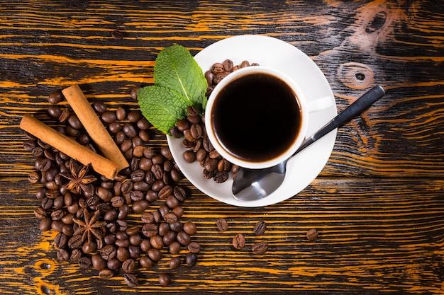 Свежезаваренная чашка кофе эспрессо с обжаренными цельными кофейными зернами, мятой, звездчатым анисом и пряностями корицы на деревенском деревянном столе, вид сверху