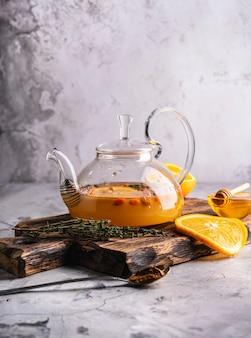Свежезаваренный облепиховый чай в прозрачном чайнике с фруктами