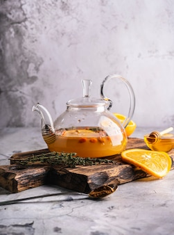 Freshly brewed sea buckthorn tea in a transparent teapot with fruits